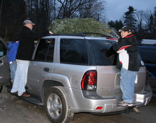 Cam and daddy tieing the tree to the car